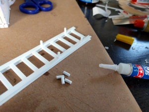 Gluing pegs to the rails.